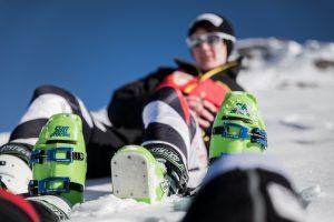 Noemi im HIntergrund unscharf im Schnee. Im Vordergrund die grün leuchtenden Dalbello Skischuhe von Ihr und Ihrem Guide