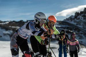 Sehbehinderte Skifahrer werden von Begleitläufern die Piste hinunter geführt oder geleitet